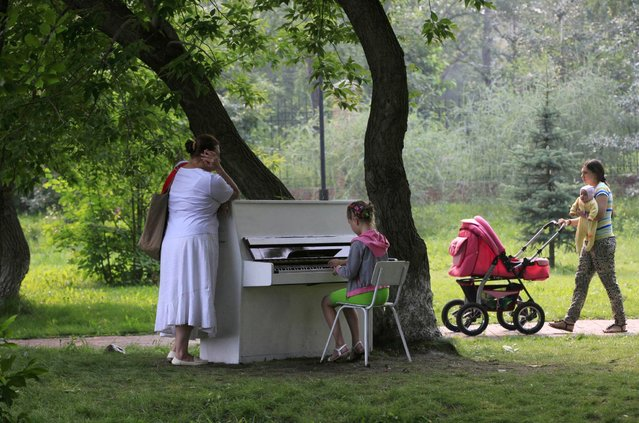 "A girl plays piano in the park in Russia's Siberian city of Krasnoyarsk, August 7, 2013. A group of young enthusiasts bought an old Soviet-made piano, adjusted it, painted white and placed in a park for free use by all visitors. The instrument is covered with a plastic foil at night and during rains. This is the group's first step in their project ""Free city entertainments"", local media said. (Photo by Ilya Naymushin/Reuters)"