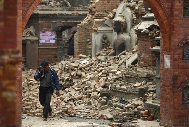 A man cries as he walks on the street while passing through a damaged statue of Lord Buddha a day after an earthquake in Bhaktapur, Nepal April 26, 2015. (Photo by Navesh Chitrakar/Reuters)