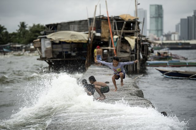 Children living on houses erected on the sea wall of Manila Bay play with waves caused by the Tropical Depression Henry that brought heavy rains in Metro Manila and the northern part of Luzon on July 16, 2018. (Photo by Noel Celis/AFP Photo)