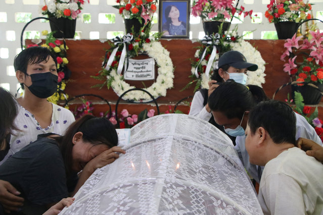 """People mourn over the body of a woman who was killed during a clash with Myanmar's security forces, before her cremation in Yangon, Myanmar, Monday, March 29, 2021. Over 100 people across the country were killed by security forces on Saturday alone, including several children — a toll that has prompted a U.N. human rights expert to accuse the junta of committing """"mass murder"""" and to criticize the international community for not doing enough to stop it. (Photo by AP Photo/Stringer)"""