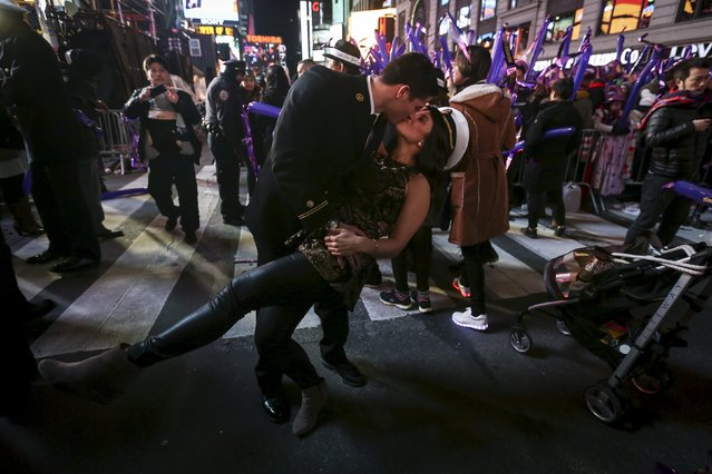 United States Navy Midshipman Mason Kraft dips Cassidy Cunningham as they pose for a photo in Times Square during New Year's Eve celebrations in the Manhattan borough of New York, December 31, 2015. (Photo by Carlo Allegri/Reuters)