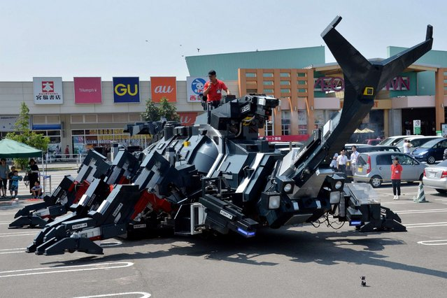 """A large beetle-shaped robot """"Kabutom RX-03"""", made by Japanese engineer Hitoshi Takahashi, is demonstrated in Higashi Ibaraki province, Japan, on August 15, 2013.The robot is 11-meters in length and weighing 17-tonnes, can walk with its six legs and can also blow smoke from its nose. (Photo by Yoshikazu Tsuno/AFP Photo)"""