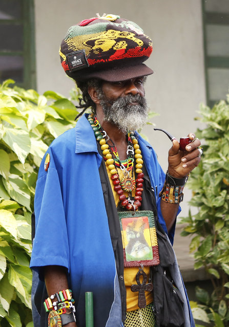 A member of the Rastafarian movement waits for the unveiling of a statue of late reggae legend Bob Marley in Kingston February 8, 2015. Jamaicans started to celebrate the 70th anniversary of Marley's birth on Friday with a jamming session at his former home and a string of free concerts as the Caribbean island continues to wrestle over his place in its pantheon of heroes. (Photo by Gilbert Bellamy/Reuters)