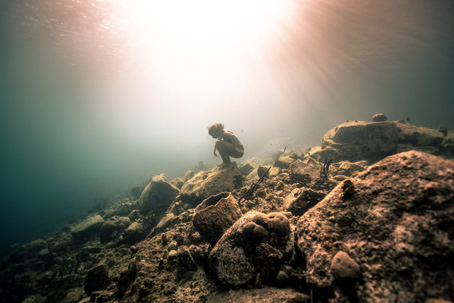 A diver sits on rocks on the ocean floor as the sunlight beams through the water. (Photo by Alex Voyer/Caters News Agency)