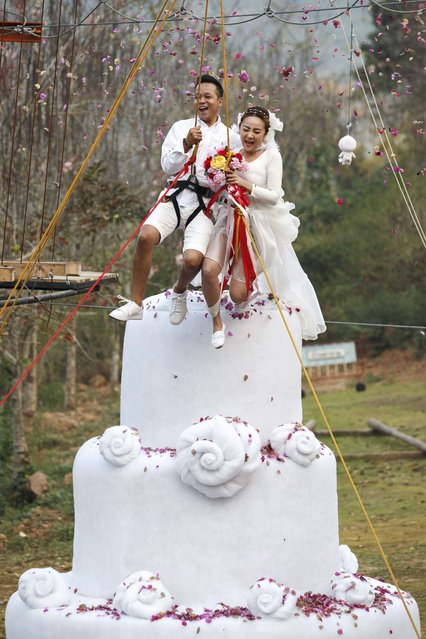 Groom Chaiyut Phuangphoeksuk and bride Prontathourn Pronnapatthun, with safety harnesses, jump from the top of a 3.5-metre tall wedding cake sculpture during their wedding ceremony at a resort in Ratchaburi province February 13, 2015. (Photo by Athit Perawongmetha/Reuters)