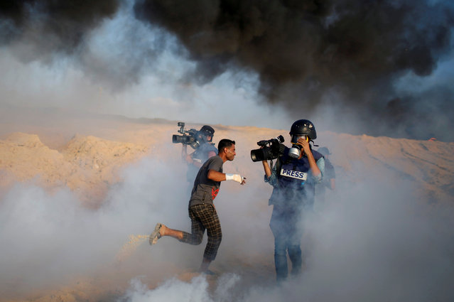 Cameramen film as a Palestinian demonstrator reacts to tear gas fired by Israeli troops during a protest calling for lifting the Israeli blockade on Gaza, on a beach near the maritime border with Israel, in the northern Gaza Strip September 10, 2018. (Photo by Mohammed Salem/Reuters)