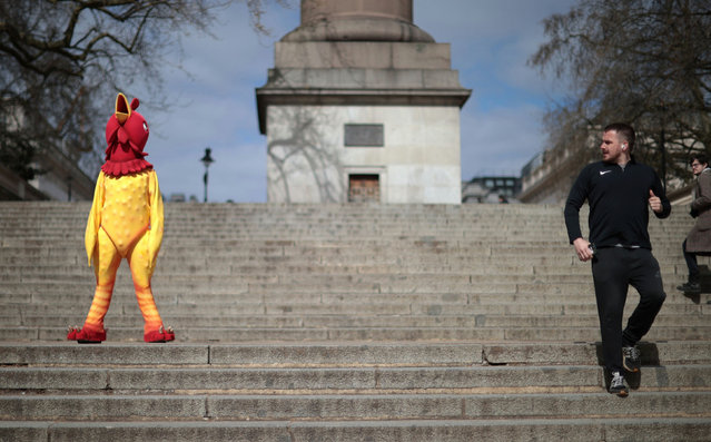 A man jogs past person dressed in a chicken costume on Good Friday in London, Britain, April 2, 2021. (Photo by Hannah McKay/Reuters)