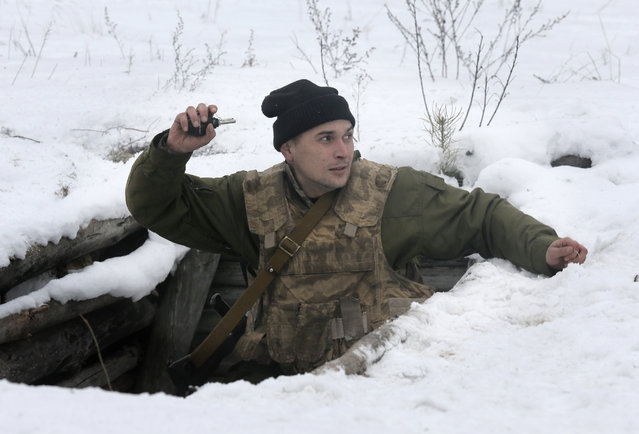 A newly mobilized Ukrainian soldier shows his skills during military drills at a base in Desna 100km north from Kiev, Ukraine, Friday, February 13, 2015. (Photo by Efrem Lukatsky/AP Photo)