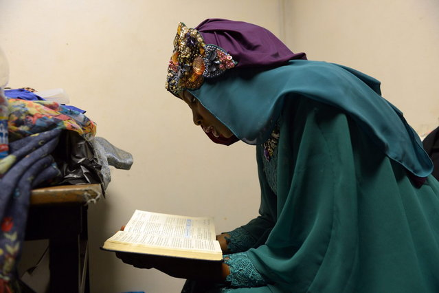 Contestant of the Muslimah World 2013, Obabiyi Aishah Ajibola of Nigeria, recites a copy of the Koran while contestants wait for a grand final during the Muslimah World competition in Jakarta on September 18, 2013. (Photo by Adek Berry/AFP Photo)