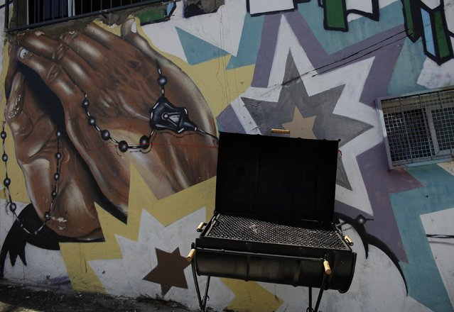 A grill made from an old oil barrel is seen next to graffiti in Brasilandia slum, in Sao Paulo February 11, 2015. (Photo by Nacho Doce/Reuters)