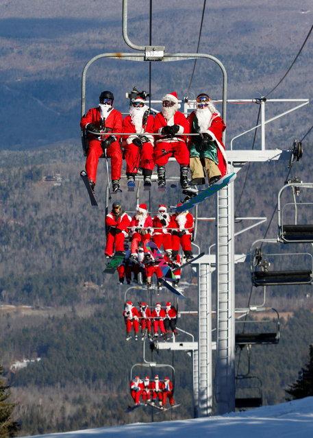 Skiers and snowboarders dressed as Santa ride up the ski lift as they participate in a charity run down a slope at Sunday River Ski Resort in Newry, Maine, U.S., December 4, 2016. (Photo by Joel Page/Reuters)