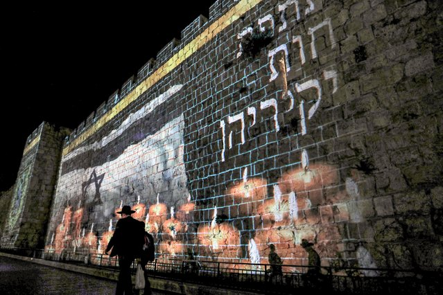 A projection of an Israeli flag flying before lit candles is displayed on the old city walls of Jerusalem on May 2, 2021, as Israel declares a national day of mourning for victims of a stampede during the Lag BaOmer holiday at Mount Meron. The deadly crush at Mount Meron in northern Israel has been described as one of the worst peacetime disasters since the nation's founding in 1948. The stampede broke out as tens of thousands of mostly ultra-Orthodox Jews thronged the reputed tomb of Rabbi Shimon Bar Yochai to commemorate the second-century Talmudic sage's death and mark Lag BaOmer holidays. (Photo by Ahmad Gharabli/AFP Photo)