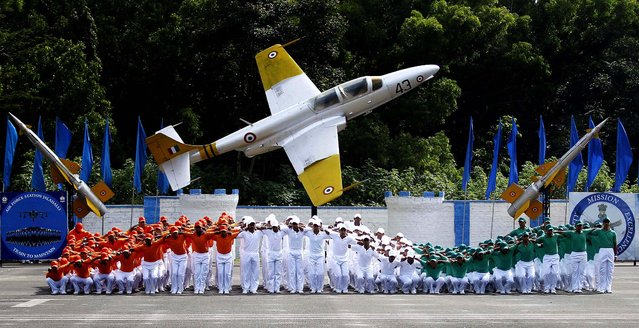 Indian Air Force trainees dressed in the Indian tri-colored flag perform during the passing out parade ceremony of their seniors in Bangalore, on September 27, 2013. (Photo by Aijaz Rahi/Associated Press)