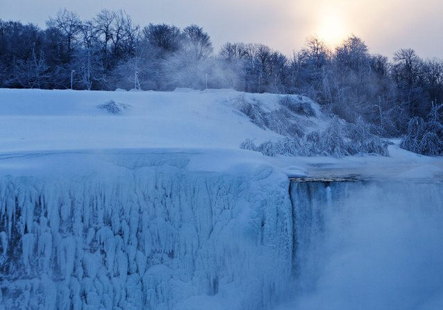 "The sun rises over masses of ice formed around the Canadian ""Horseshoe"" Falls in Niagara Falls, Ontario, Canada, Thursday, February 19, 2015. (Photo by Aaron Lynett/AP Photo/The Canadian Press)"