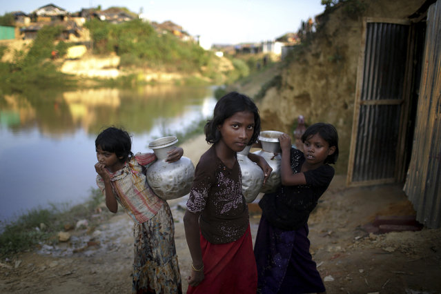 In this Sunday, November 19, 2017, file photo, Rohingya Muslim girls carry water pots in Kutupalong refugee camp in Bangladesh. (Photo by Wong Maye-E/AP Photo)