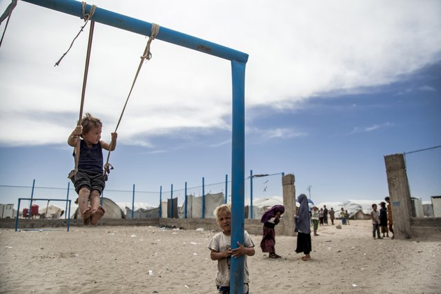 Children play at al-Hol camp that houses some 60,000 refugees, including families and supporters of the Islamic State group, many of them foreign nationals, in Hasakeh province, Syria, Saturday, May 1, 2021. Kurdish officials say security has improved at the sprawling camp in northeast Syria, but concerns are growing of a coronavirus outbreak in the facility. (Photo by Baderkhan Ahmad/AP Photo)