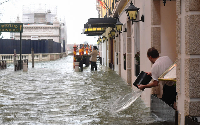 A man empties a bucket of water on a flooded street during a high- water (Acqua Alta) alert in Venice on October 29, 2018. (Photo by Miguel Medina/AFP Photo)