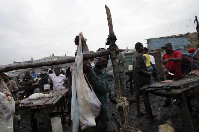 Jean Libonet hangs a butchered goat to be sold at La Saline slaughterhouse in Port-au-Prince, Haiti, March 19, 2015. (Photo by Andres Martinez Casares/Reuters)