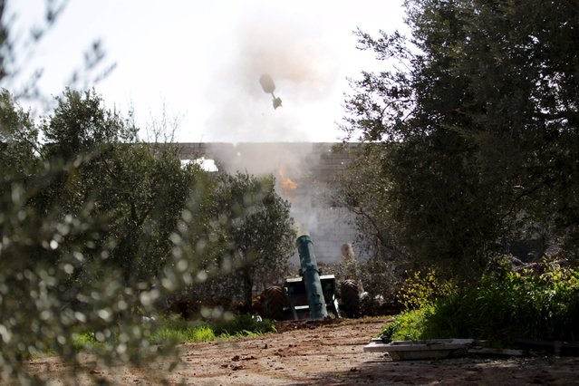 Islamic Ahrar al-Sham fighters fire a locally made weapon towards forces loyal to Syria's president Bashar Al-Assad on the frontline of Idlib city in northern Syria, where they announced a battle to liberate the city March 21, 2015. (Photo by Khalil Ashawi/Reuters)
