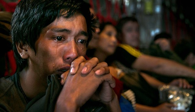 A man sits crying on a packed C130 aircraft as emotions take over as he and hundreds of other victims of super Typhoon Haiyan are evacuated from the area on November 12 in Tacloban. (Photo by Paula Bronstein/Getty Images)