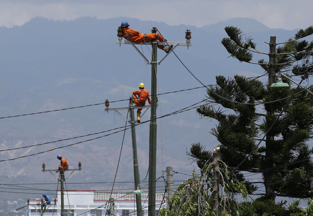In this Saturday, October 6, file photo, a worker rests on top of a pole as they restore electricity at the earthquake-hit Balaroa neighborhood in Palu, Central Sulawesi, Indonesia. (Photo by Aaron Favila/AP Photo)