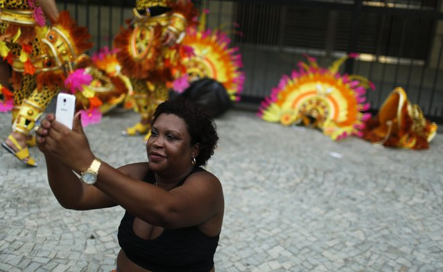 A reveller takes a selfie as she waits for the first night of the Carnival parade of samba schools in Rio de Janeiro's Sambadrome February 15, 2015. (Photo by Pilar Olivares/Reuters)