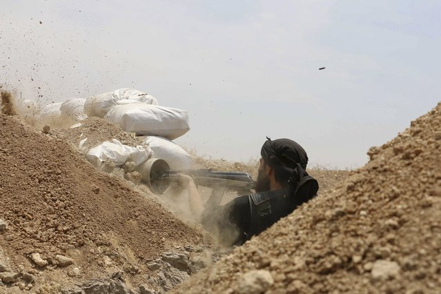 A Jaysh al-Islam (Army of Islam) rebel fighter fires his weapon towards forces loyal to Syria's President Bashar Al-Assad at the Tal-Kurdi frontline in the Eastern Ghouta of Damascus, May 10, 2015. (Photo by Amer Almohibany/Reuters)