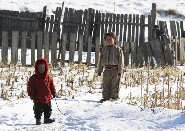 North Korean children stand after snowfall along the banks of the Yalu River, near the North Korean Sakchu County, December 17, 2014. Picture taken on the China side of the Yalu River. (Photo by Jacky Chen/Reuters)