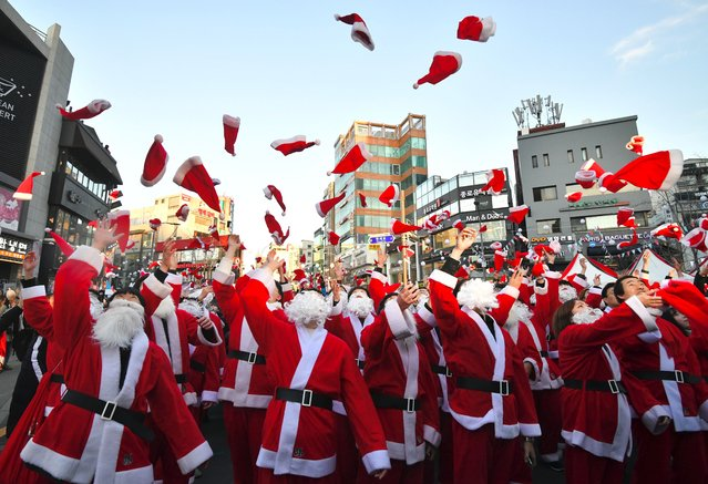 South Korean volunteers in Santa Claus outfits throw Santa hats during a ceremony before the delivery of Christmas gifts in Seoul on December 24, 2018. The volunteers will deliver Christmas gifts to 1,200 kids from 800 poor families in Seoul on Christmas eve. (Photo by Jung Yeon-je/AFP Photo)