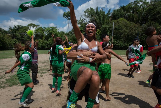 Female indigenous players of Satere Mawe tribe celebrate their victory of the final of Peladao, the amateur football tournament, in Manaus, Amazonas state, Brazil, on November 24, 2013. (Photo by Yasuyoshi Chiba/AFP Photo)