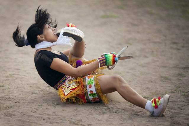 "A ""scissors"" dancer grabs her shoe with her mouth while performing in a national scissors dance competition in the outskirts of Lima December 1, 2013. (Photo by Enrique Castro-Mendivil/Reuters)"