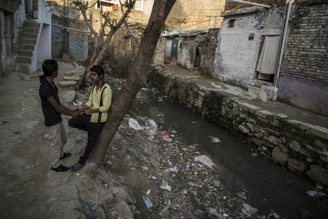 Teenagers chat beside an open sewer at a slum in Islamabad March 12, 2015. (Photo by Zohra Bensemra/Reuters)
