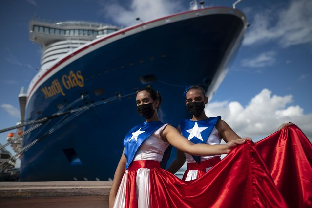 Ivanelis Jimenez, front, and Veronica Barreto pose for the camera wearing Puerto Rican flag dresses as they welcome passengers exiting Carnival's Mardi Gras cruise ship, docked in the bay of San Juan, Puerto Rico, Tuesday, August 3, 2021, marking the first time a cruise ship visits the U.S. territory since the COVID-19 pandemic began. (Photo by Carlos Giusti/AP Photo)