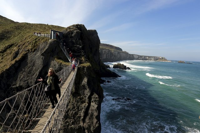 Tourists make their way across Carrick-a-Rede Rope Bridge on the Causeway coast, north of Belfast April 8, 2015. The bridge is suspended 30 metres above sea level and was built 350 years ago by salmon fishermen, according to conservation organisation National Trust. (Photo by Cathal McNaughton/Reuters)