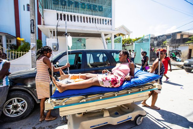 A woman injured during the 7.2 magnitude earthquake lies on a stretcher in Les Cayes, Haiti on August 14, 2021. (Photo by Ralph Tedy/Reuters)