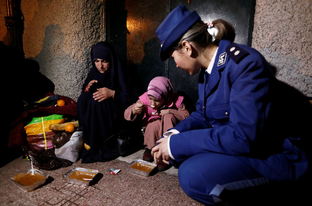 """Djamila Boubakeur, a police lieutenant (R), kneels as she watches a homeles girl eat during """"Winter Soup"""", a charity campaign to distribute meals by police to homeless people, in Algiers, Algeria January 11, 2017. (Photo by Zohra Bensemra/Reuters)"""
