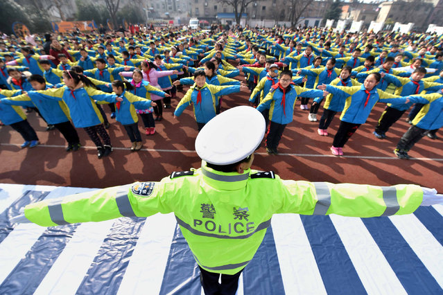 A policeman teaches traffic rules to primary school students at a school in Hefei, Anhui province, February 25, 2016. (Photo by Reuters/China Daily)