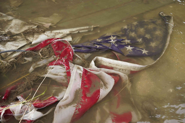 In the aftermath of Hurricane Ida, an American flag floats in a puddle of flood water Wednesday, September 1, 2021, in Myrtle Grove, La. (Photo by Steve Helber/AP Photo)
