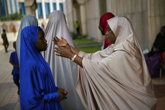 """A Nigerian woman attends Friday prayers at the central mosque is security checked a day prior to the election, in Abuja, Nigeria, Friday February 15, 2019.  Nigeria surged into the final day of campaigning ahead of Saturday's election, as President Muhammadu Buhari made one last pitch to stay in office while top challenger Atiku Abubakar shouted to supporters: """"Oh my God! Let them go! Let them go""""! (Photo by Jerome Delay/AP Photo)"""