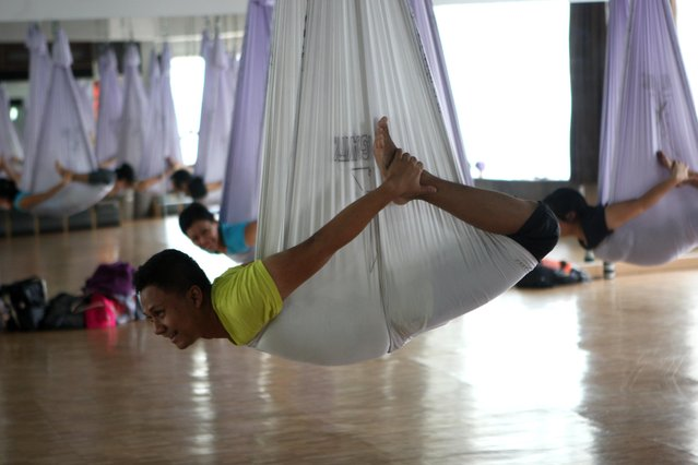 Yoga Instructor Ari shows a yoga pose on the hammock during the Anti-Gravity yoga class at Svarga e-Motion Sanctuary at Dharmawangsa Square, Jakarta, Saturday, April 18, 2015. (Photo by Jurnasyanto Sukarno/JG Photo)