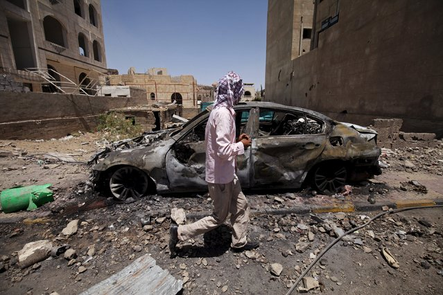 A man walks past a car damaged by an air strike on Monday which hit a nearby army weapons depot, in Sanaa April 21, 2015. (Photo by Mohamed al-Sayaghi/Reuters)