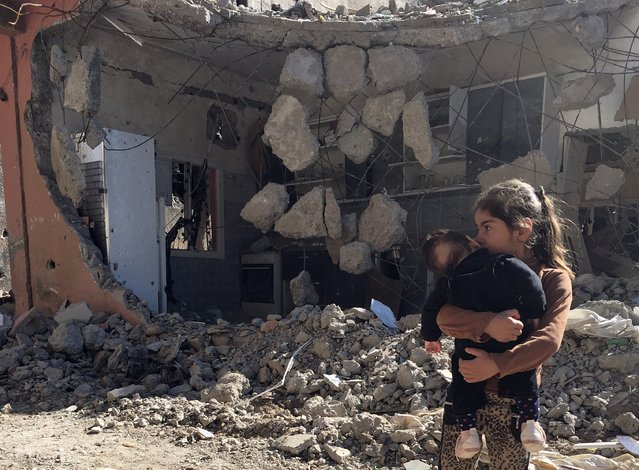 A young girl holds a child in front of a ruined house in Cizre, Turkey, Wednesday, March 2, 2016. Turkish authorities on Wednesday scaled down a 24-hour curfew imposed on the mainly Kurdish town of Cizre in southeast Turkey, nearly three weeks after declaring the successful conclusion of military operations there. The stench of death and the smell of gunpowder rose from mounds of rubble Wednesday as residents of the Turkish town of Cizre returned to find many of their homes obliterated amid Turkey's efforts to crush Kurdish militants. (Photo by Ayse Wieting/AP Photo)