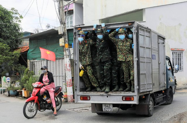 Vietnamese soldiers look out from a truck as they deliver food in strict lockdown areas amid the coronavirus pandemic in Ho Chi Minh City, Vietnam on August 24, 2021. (Photo by Reuters/Stringer)
