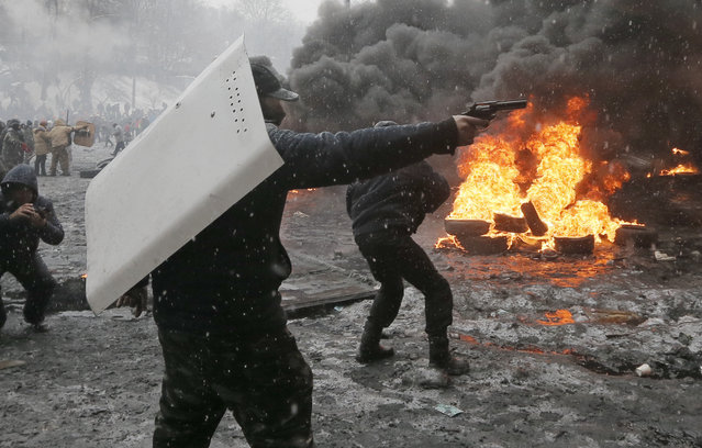 A protester points a handgun during a clash with police in central Kiev, Ukraine, Wednesday, January 22, 2014.  (Photo by Efrem Lukatsky/AP Photo)