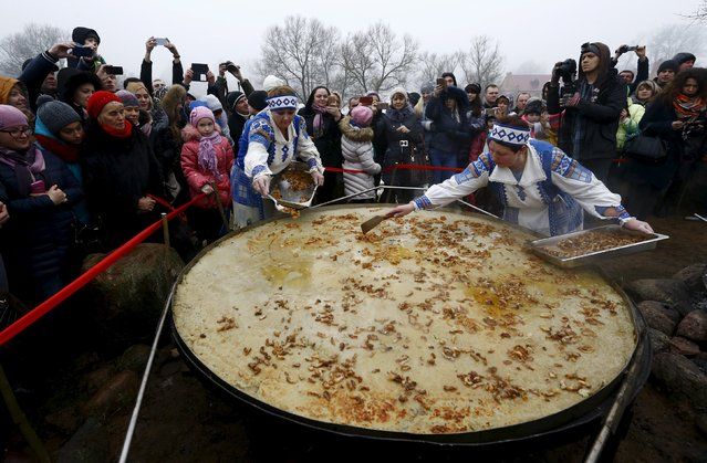 Employees cover bacon on fried dranik, a potato pancake that is the national dish of Belarus, in the Sula History Park near the village of Sula, Belarus March 7, 2016. (Photo by Vasily Fedosenko/Reuters)