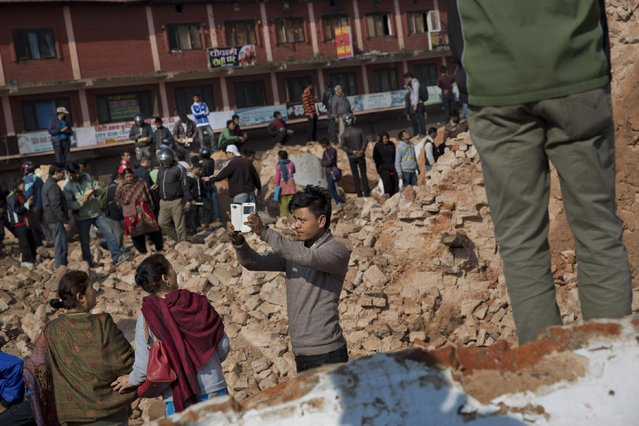 A man takes a selfie at the historic Dharahara Tower, a city landmark, that was damaged in Saturday's earthquake in Kathmandu, Nepal, Monday, April 27, 2015. (Photo by Bernat Armangue/AP Photo)