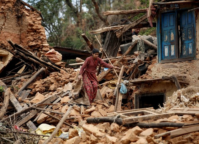 A resident tries to climbs down on the debris of her house at a village following Saturday's earthquake in Sindhupalchowk, Nepal, April 28, 2015. (Photo by Danish Siddiqui/Reuters)