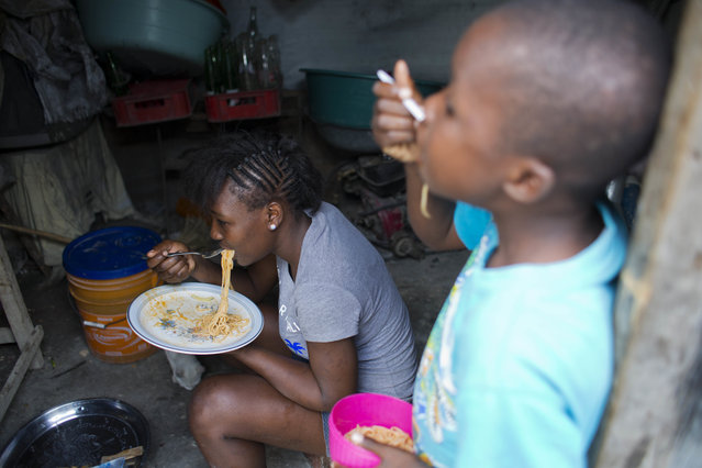 In this December 6, 2016 photo, Adrienne St. Fume's 16-year-old daughter Rigencia, and 8-year-old nephew Kenson, dig into a meal of pasta inside the Delmas tent camp set up nearly seven years ago for people displaced by the 2010 earthquake, in Port-au-Prince, Haiti. The mother of three said she figured the Delmas shelter would be temporary as they and the rest of Port-au-Prince recovered from the January 2010 earthquake. But St. Fume has yet to find a way out. (Photo by Dieu Nalio Chery/AP Photo)