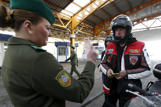 A Belarussian border guard checks a passport of a member of the Night Wolves motorcycle club, who is participating in a group bike ride to commemorate the 70th anniversary of the victory over Nazi Germany in World War Two, at a border crossing with Poland near Brest April 27, 2015. (Photo by Vasily Fedosenko/Reuters)