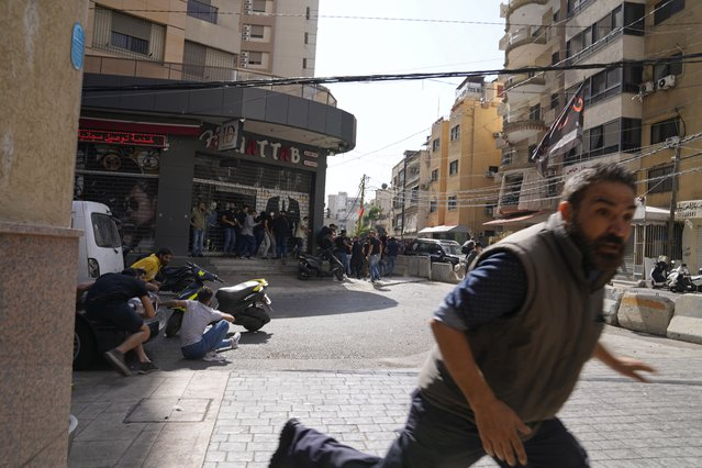 A man runs to take cover as supporters of a Shiite group allied with Hezbollah fire weapons during armed clashes that erupted during a protest in the southern Beirut suburb of Dahiyeh, Lebanon, Thursday, Octoner 14, 2021. It was not immediately clear what triggered the gunfire, but tensions were high along a former civil war front-line between Muslim Shiite and Christian areas. (Photo by Hassan Ammar/AP Photo)